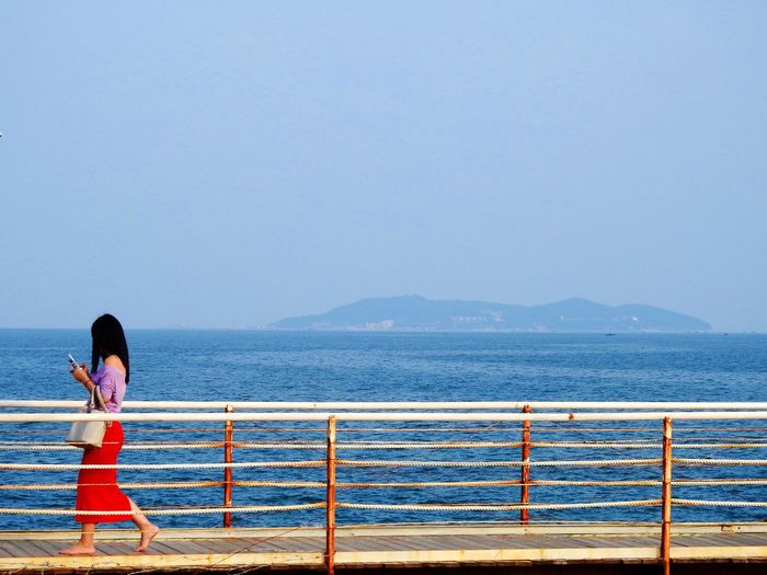 Woman walking on bridge by sea against sky