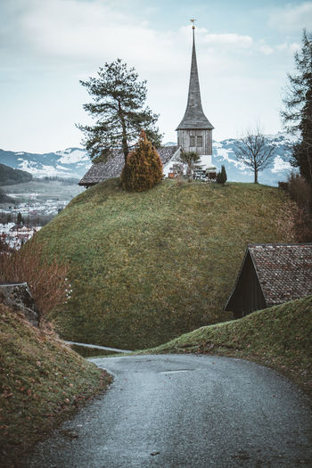 Low angle view of church on hill against cloudy sky