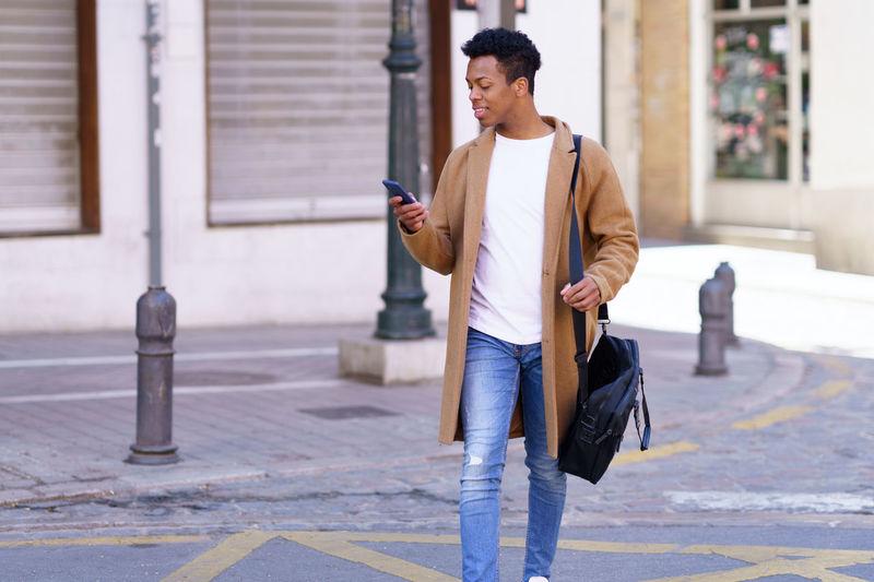 Full length of man using mobile phone on sidewalk