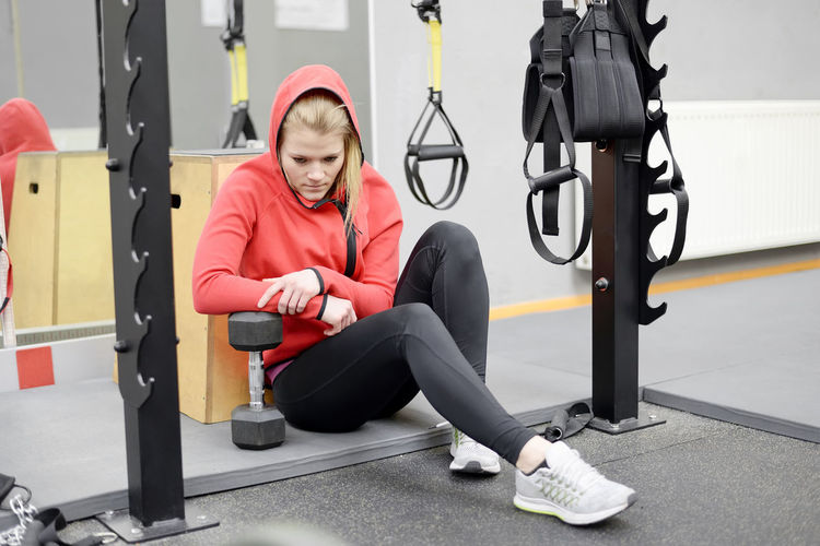 Full Length Of Young Woman Sitting In Gym