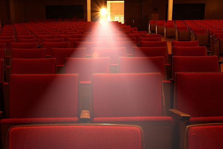Light falling from projector on seats of movie theater