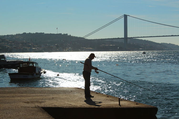 Side view of man fishing at harbor with bosphorus bridge in background