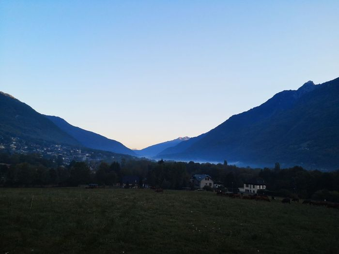 Scenic view of field and mountains against clear sky