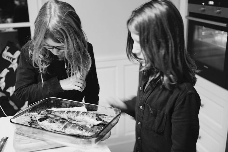Girls Standing By Fish In Tray At Table