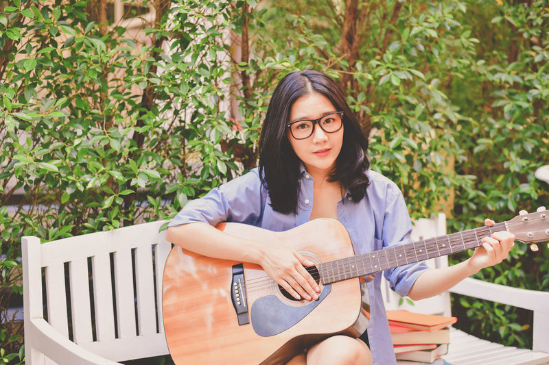 Beautiful Woman Casual Clothing Day Front View Guitar Hair Hairstyle Leisure Activity Lifestyles Looking At Camera Music Musical Equipment Musical Instrument One Person Outdoors Playing Portrait Real People Sitting String Instrument Young Adult Young Women