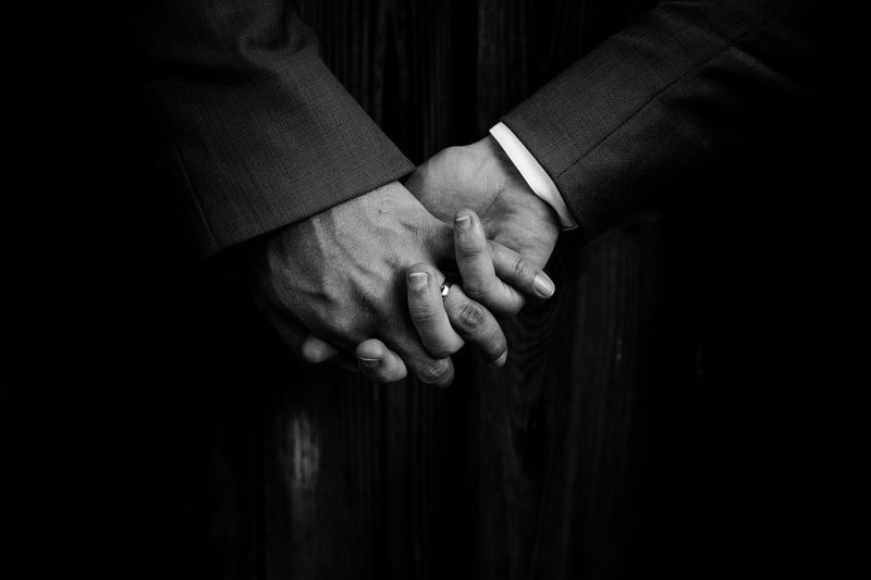 Close-Up Of Gay Men Holding Hands In Dark