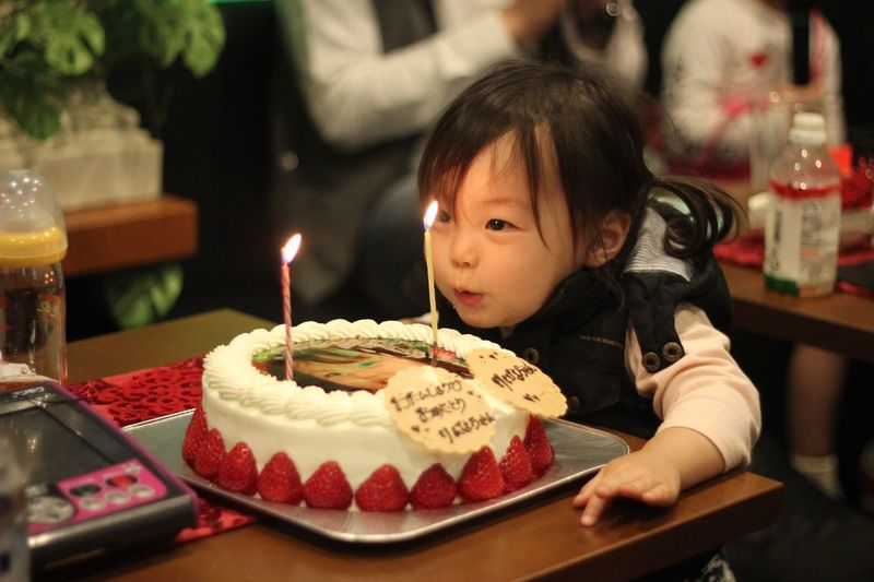 Cute baby girl blowing candles on cake