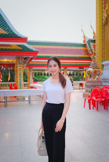 Portrait of smiling young woman standing against temple