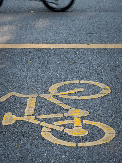 Bicycle symbol on street, Bicycle road sign. Sign Road Transportation Symbol City Communication Disabled Sign Street Day Marking Yellow Road Marking High Angle View Disabled Access No People Asphalt Guidance Outdoors Mode Of Transportation Direction Dividing Line