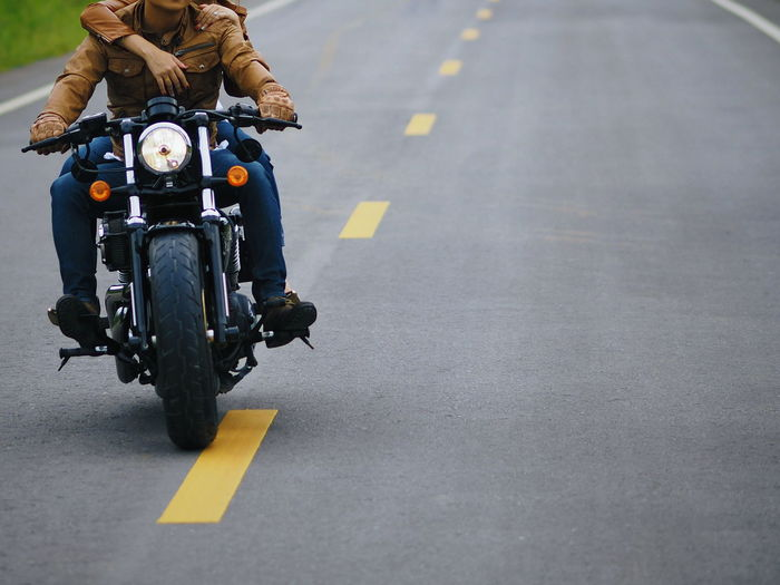 Low Section Of Couple Riding Motorcycle On Road