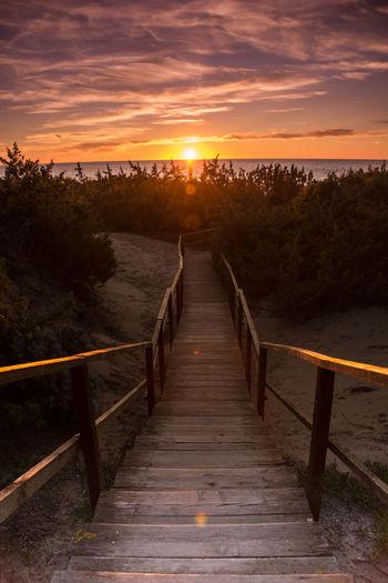 Wooden bridge against sky during sunset