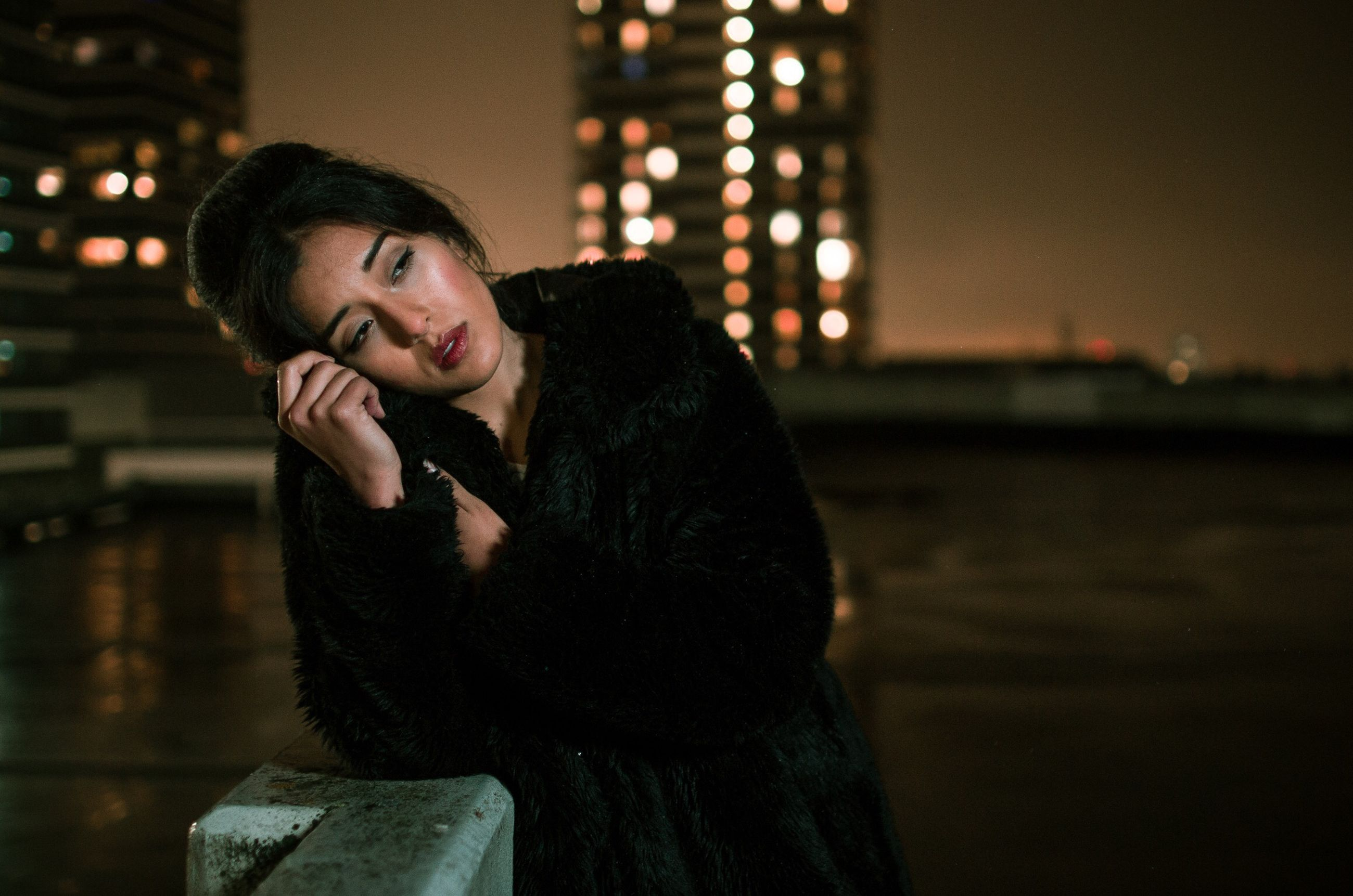 one person, young adult, night, focus on foreground, real people, lifestyles, leisure activity, waist up, illuminated, young women, looking, portrait, looking away, hair, casual clothing, front view, beauty, beautiful woman, hairstyle, contemplation, warm clothing