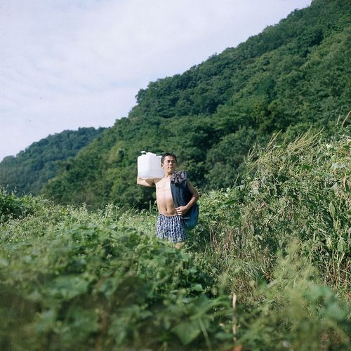 Shirtless young man carrying container while standing amidst plants against mountain