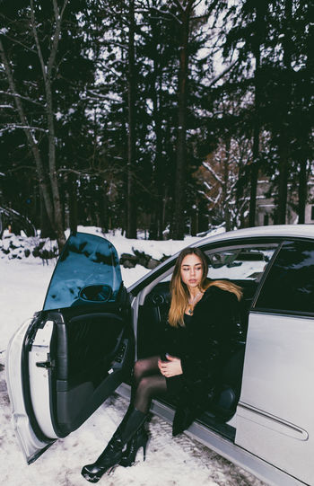 Full length of young woman sitting on car seat during winter