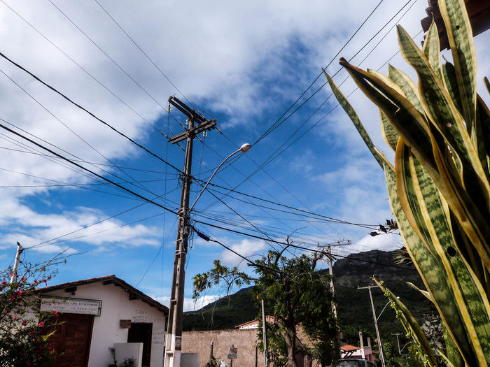 Low angle view of telephone pole and street light