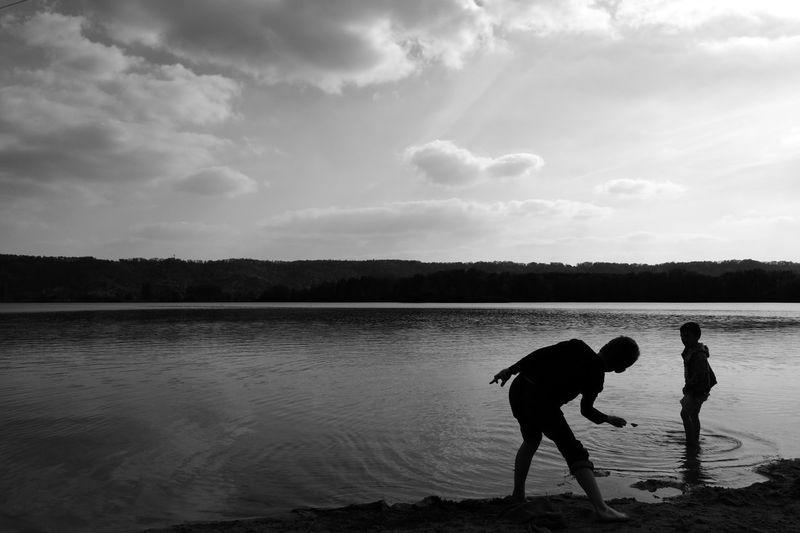 Boys Playing In Lake During Sunset