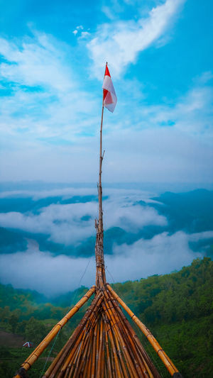Panoramic view of flag on mountain against sky