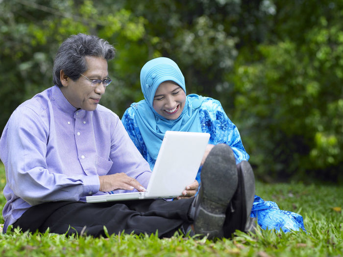 Smiling Couple Using Laptop In Park