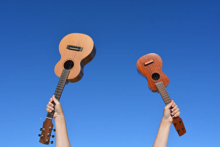Low angle view of guitar against clear blue sky