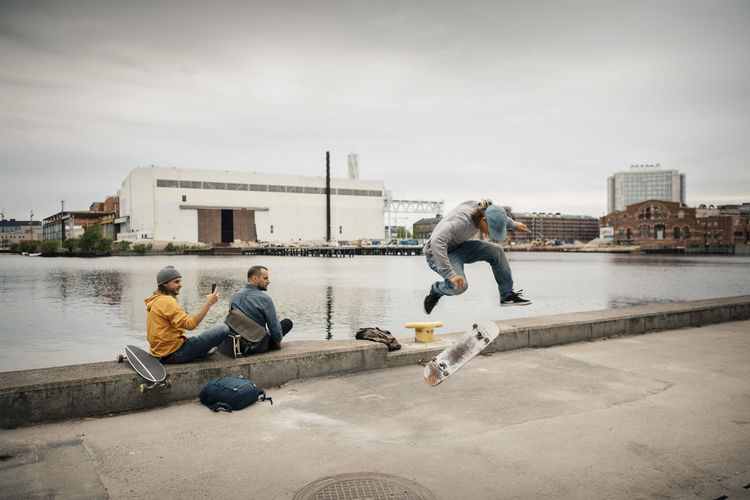 People on riverbank against sky in city