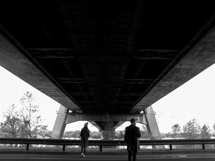 Low angle view of people standing under bridge