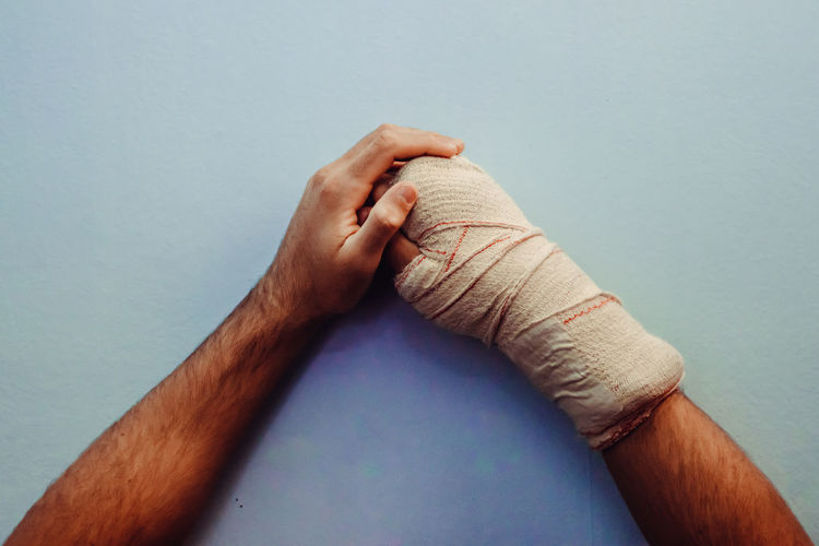 Cropped hand of man wrapped in bandage on table