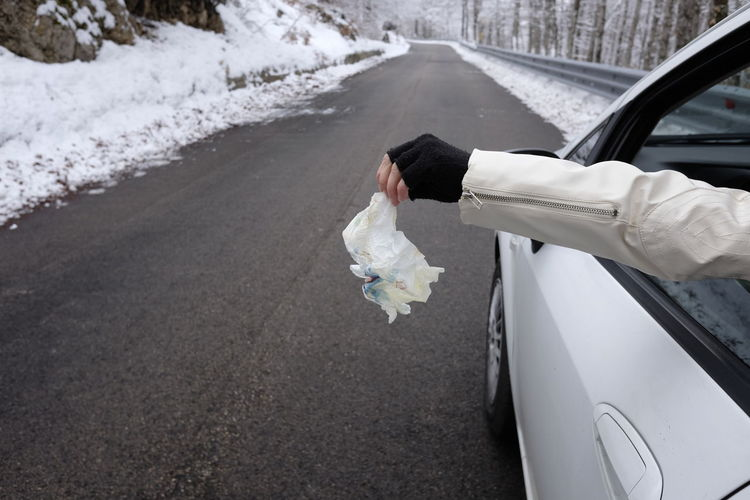 Cropped hand holding crumpled tissue paper outside car window on road
