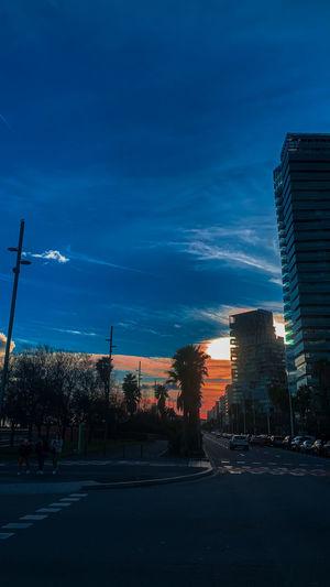 Street amidst buildings against blue sky at dusk