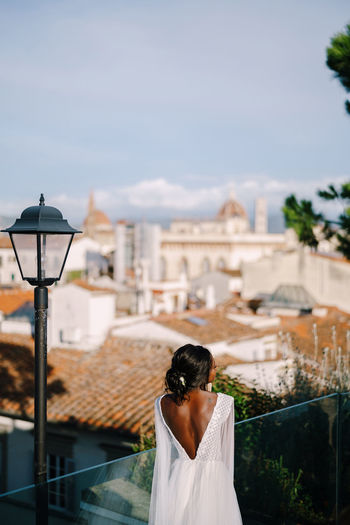 Rear view of bride looking at townscape