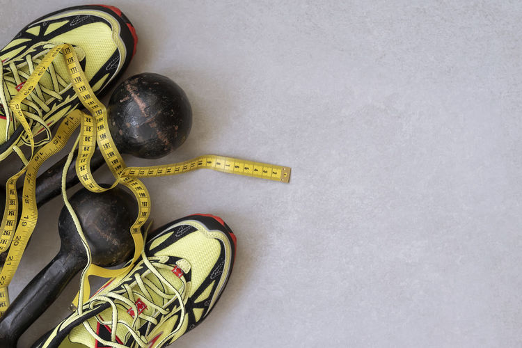 Sneakers, old dumbbells and tape measure, top view, concept of healthy lifestyle. Sports concept, copy space High Angle View Still Life Tape Measure No People Copy Space Sport Close-up Helmet Indoors  Directly Above Sports Equipment Yellow Headwear Text Sneakers Old Dumbbell Tape Measure Top View Healthy Lifestyle Fit Fitness