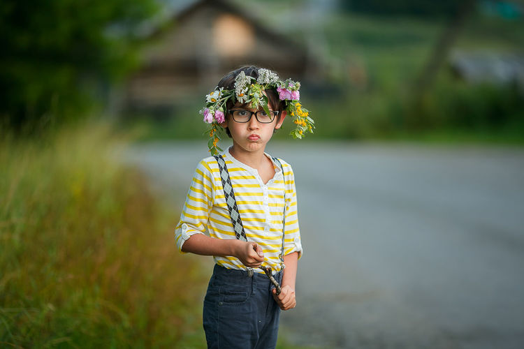 Portrait of cute girl wearing flower while standing outdoors