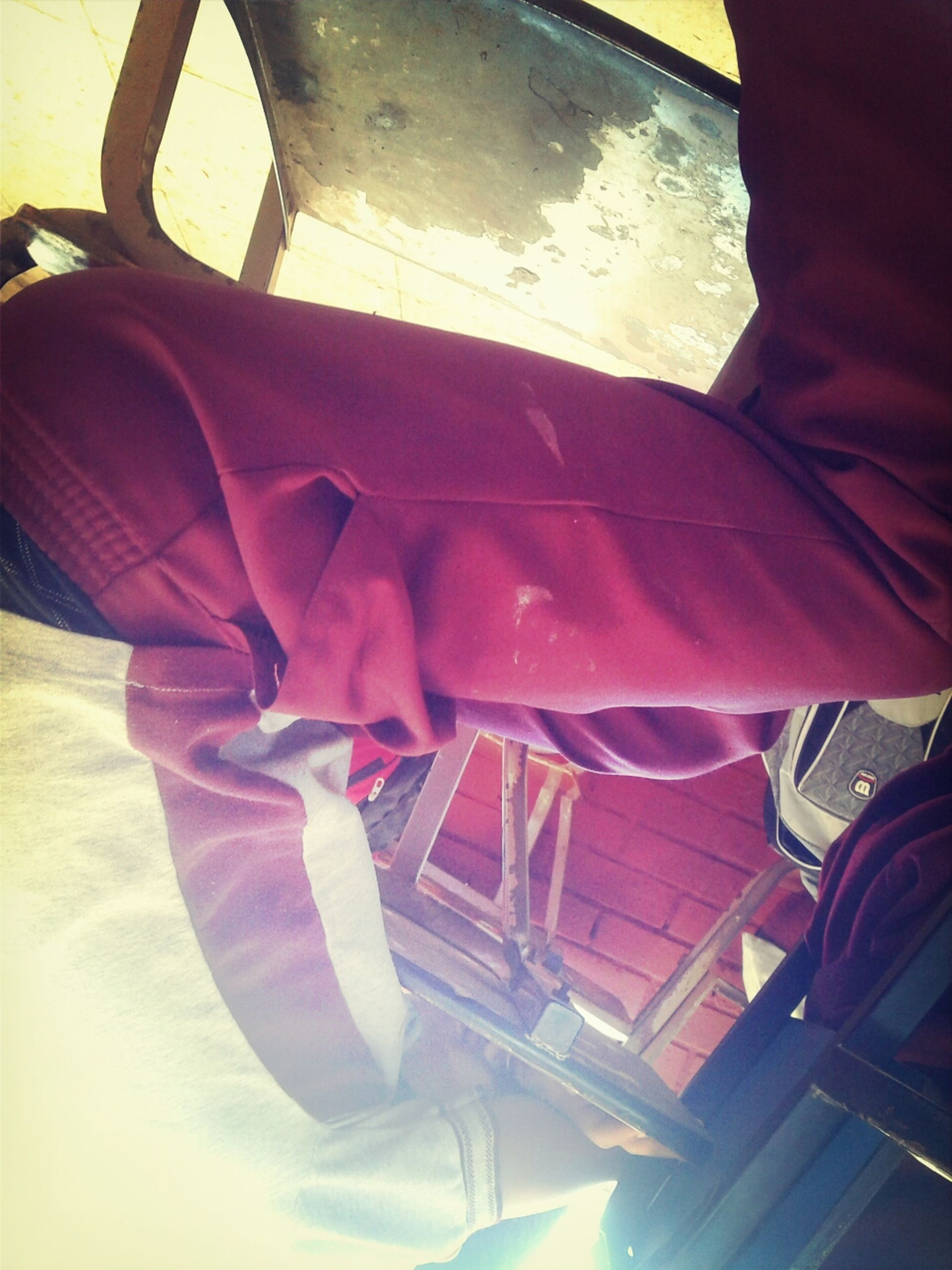 indoors, low section, person, sitting, transportation, relaxation, chair, seat, high angle view, sunlight, mode of transport, vehicle interior, lifestyles, shoe, land vehicle, men, red, travel