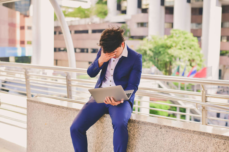 Stressed businessman using laptop in city