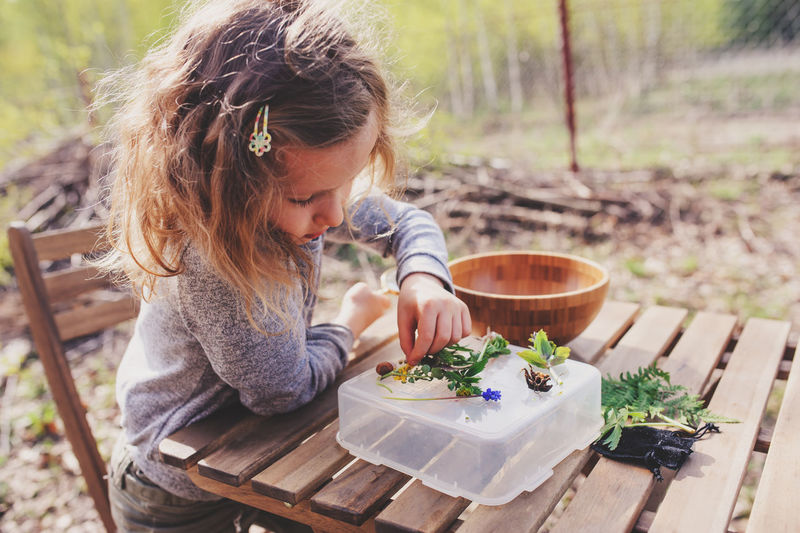 Close-up of girl playing with leaves on wooden table at yard