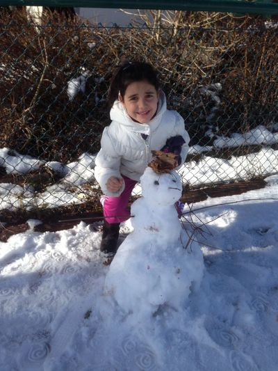 Portrait Of Cute Girl Making Snowman During Winter