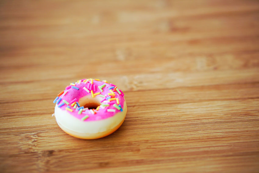 Sweet Food Sweet Food And Drink Food Indulgence Wood - Material Indoors  Table Pink Color Dessert No People Donut Baked Close-up Unhealthy Eating Freshness Sprinkles Still Life Temptation Selective Focus Wood Grain Snack