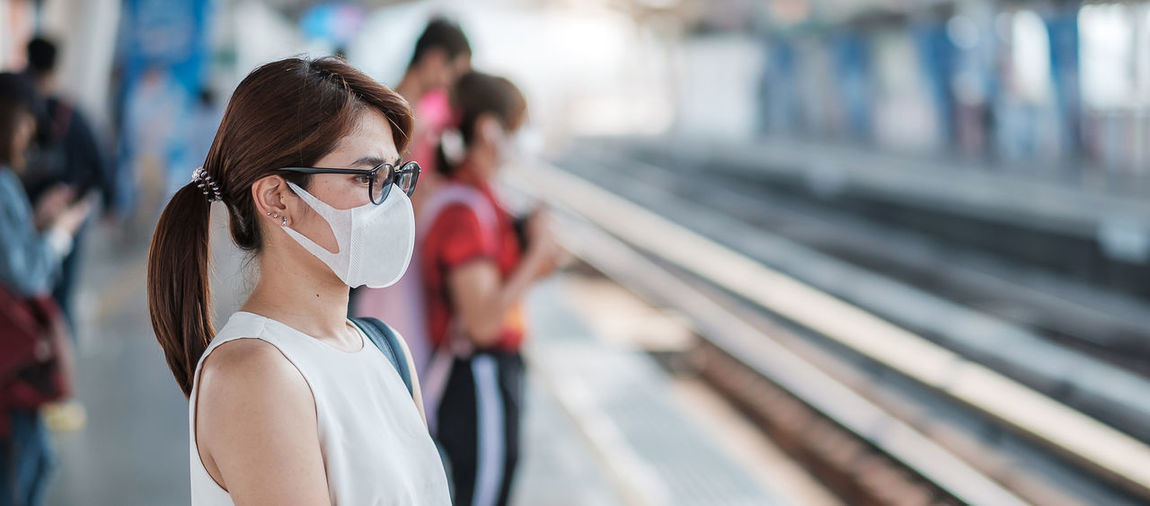 Side view of woman wearing flu mask standing outdoors