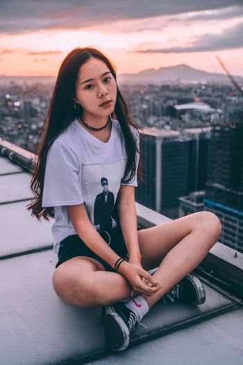 Portrait of young woman sitting on city against sky during sunset