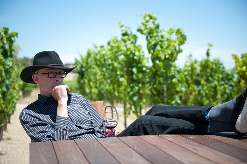 Thoughtful Man With Legs On Table Holding Wineglass In Vineyard