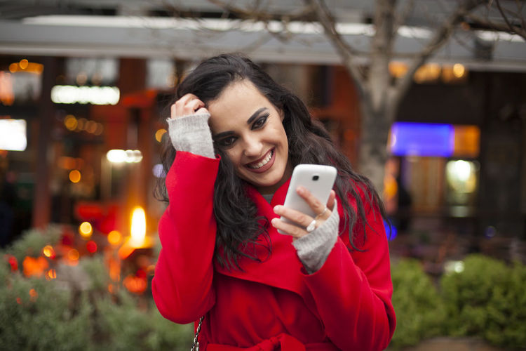Portrait of smiling young woman using mobile phone while standing on city street