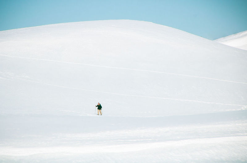 Person on snowcapped mountain against sky