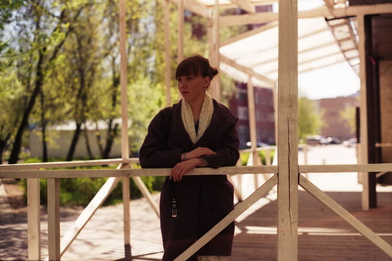 Thoughtful woman standing by railing at porch