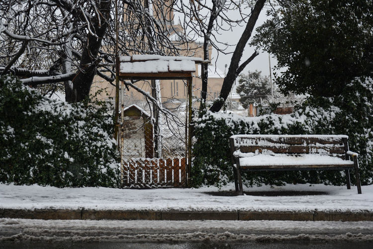 Empty park bench by building during winter