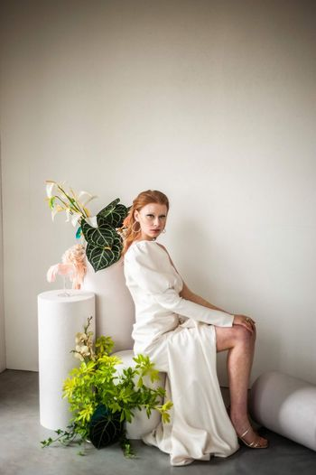 Portrait of woman sitting by potted plant against wall