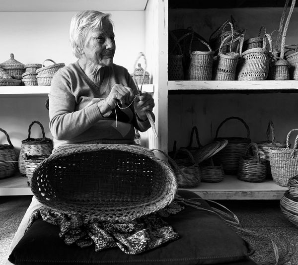 Woman Making Wicker Baskets While Sitting On Table At Home