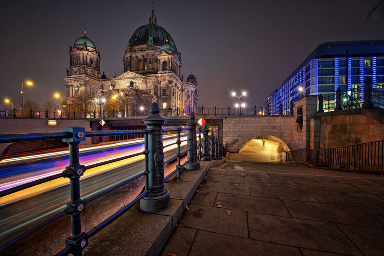Light trails in canal by berlin cathedral against sky at night