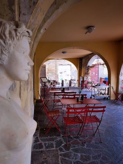 Arch Window Architecture Built Structure Day Open Air Restaurant Red Chairs Statues