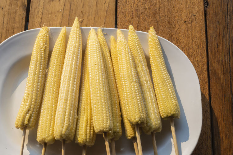 Baby corn on skewers in a white plate
