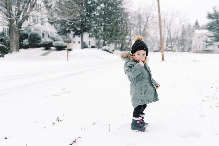 Full length of child on snow covered trees