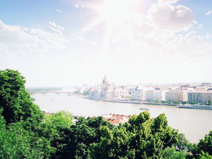 Hungarian Parliament Building By Danube River In City Against Sky